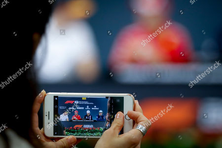 A journalist uses a mobile phone to take a photo of (L-R) Belgian Formula One driver Stoffel Vandoorne of McLaren, German Formula One driver Sebastian Vettel of Scuderia Ferrari, French Formula One driver Esteban Ocon of Sahara Force India F1 Team, and Canadian Formula One driver Lance Stroll of Williams attending a press conference ahead of the Japanese Formula One Grand Prix at the Suzuka Circuit in Suzuka, central Japan, 04 October 2018. The Japanese Formula One Grand Prix will take place on 07 October.