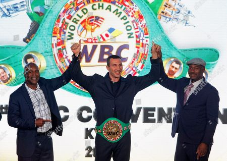 Wladimir Klitschko, Ukrainian boxing Champion(C) is seen giving the WBC honorary champion belt, while Evander Holyfield, former Boxing Champion (L) and Lennox Lewis, former Boxing Champion (R) hold his hands during ceremony of opening of the 56th WBC Convention in Kiev.