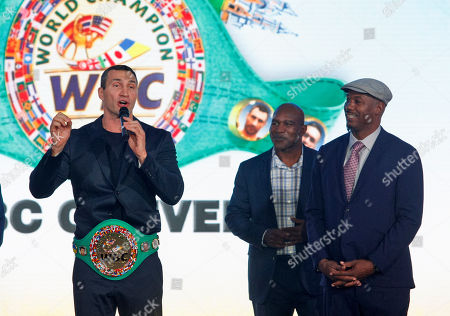 Wladimir Klitschko, Ukrainian boxing Champion(L) is seen speaking after giving the WBC honorary champion belt, while Evander Holyfield, former Boxing Champion (C) and Lennox Lewis, former Boxing Champion (R) hold his hands during ceremony of opening of the 56th WBC Convention in Kiev.