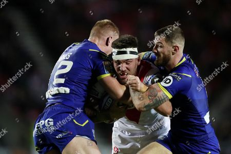 Luke Douglas of St Helens is tackled by Jack Hughes and Daryl Clark of Warrington Wolves