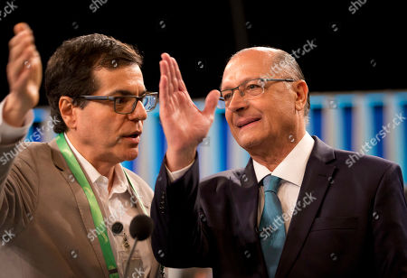 Geraldo Alckmin, presidential candidate of the Social Democratic Party, right, talks with an adviser before a live, televised presidential debate in Rio de Janeiro, Brazil, . Brazil will hold general elections on Oct. 7