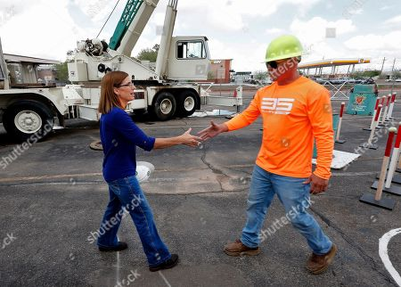 U.S. Rep. Martha McSally, R-Ariz., who is running against U.S. Rep. Kyrsten Sinema, D-Ariz., for the senate seat being vacated by retiring U.S. Sen. Jeff Flake, R-Ariz., talks to Wade Pankey at a crane manufacturing and training facility, in Phoenix. Arizona's Senate race pits Sinema, a careful politician running as a centrist in a Republican-leaning state, against McSally, a onetime Trump critic turned fan