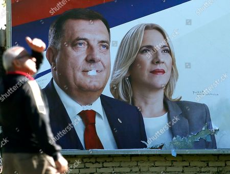 Stock Picture of A man walks by an election poster with the images of Milorad Dodik and Zeljka Cvijanovic of the Alliance of Independent Social Democrats (SNSD) in the Bosnian town of Banja Luka, 240 kms northwest of Sarajevo, . Elections in Bosnia on Sunday risk cementing the ethnic divisions of the country's brutal war, as a pro-Russian nationalist runs for the three-member presidency and politicians seeking other posts campaign on war wounds rather than reforms