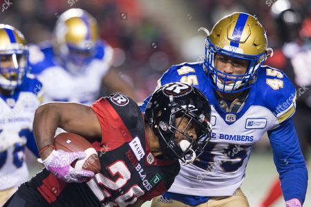 Ottawa Redblacks William Powell (29) runs with the ball while Winnipeg Blue Bombers Jovan Santos-Knox (45) closes in for a tackle during the CFL game between the Winnipeg and Ottawa Redblacks at TD Place Stadium in Ottawa, Canada. Winnipeg won in overtime by a score of 40-32
