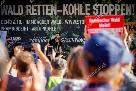 Frontsinger Johannes Strate of German music band 'Revolverheld' performs on stage as demonstrators gather around the vigil close to the forest Hambacher Forst to protest against its deforestation in Kerpen-Buir, Germany, 06 October 2018. The Higher Administrative Court in Muenster on 05 October told energy concern RWE that it must desist from clearing the Hambach Forest, pending its verdict on a lawsuit brought by environmental group 'BUND' (German Federation for the Environment and Nature Conservation). A second administrative court in Aachen overruled a police ban on an anti-coal rally near the forest, ruling in favor of a right-to-assembly appeal brought by another protest organiser, the environmental network 'Nature Friends Germany'.
