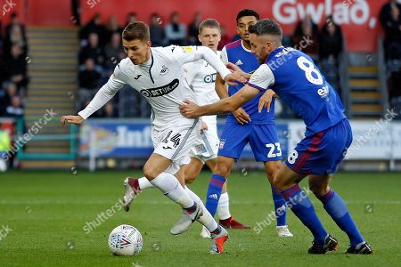 Tom Carroll of Swansea City (left) in action with Cole Skuse of Ipswich Town