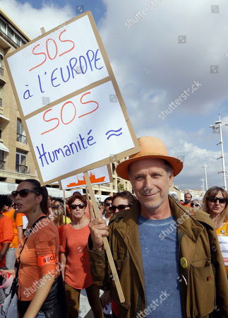 """French actor Charles Berling takes part in a gathering to support the Aquarius ship that rescues migrants operated by the humanitarian group SOS Mediterranee, in the Old-Port of Marseille, southern France, . The Aquarius which is docked in Marseille harbour, SOS Mediterranee said Thursday the Aquarius is making a stopover while waiting for a new flag and is """"determined to go back to sea as soon as possible."""" The group urged European governments to find a new flag for the vessel to secure its future after Panama's maritime authority removed the ship's registration. Placard reads """"SOS at Europe-SOS humanity"""