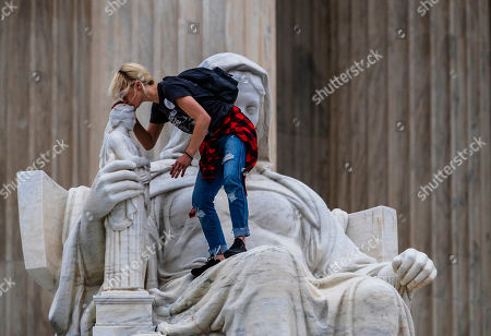 Jessica Campbell-Swanson, an activist from Denver, kisses the sculpture known as the Statue of Contemplation of Justice on the steps of the Supreme Court Building where she and others protested the confirmation of Brett Kavanaugh as the high court's newest justice, in Washington, . Kavanaugh took the oath inside the building after the bitterly polarized U.S. Senate narrowly confirmed him, delivering an election-season triumph to President Donald Trump that could swing the court rightward for a generation