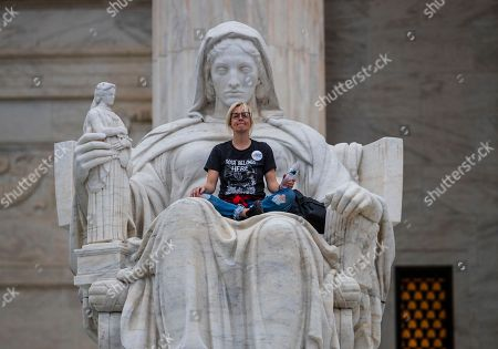 Jessica Campbell-Swanson, an activist from Denver, sits in the lap of a sculpture known as the Statue of Contemplation of Justice on the steps of the Supreme Court Building where she and others protested the confirmation of Brett Kavanaugh as the high court's newest justice, in Washington, . Kavanaugh took the oath inside the building after the bitterly polarized U.S. Senate narrowly confirmed him, delivering an election-season triumph to President Donald Trump that could swing the court rightward for a generation