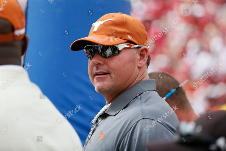 Former Texas Longhorns baseball pitcher Roger Clemens stands on the sideline of an NCAA college football game between the Texas Longhorns and Oklahoma Sooners, in Dallas, Texas