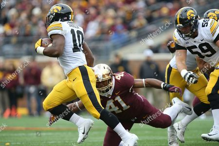 Iowa running back Mekhi Sargent escapes the tackle by Minnesota's Thomas Barber during an NCAA college football game, in Minneapolis