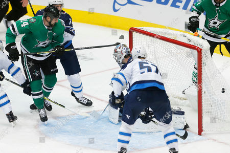Dallas Stars forward Jamie Benn (14) scores a goal as Winnipeg Jets defenseman Tyler Myers (57) and Winnipeg Jets goaltender Connor Hellebuyck (37) defend during the second period of an NHL hockey game, in Dallas