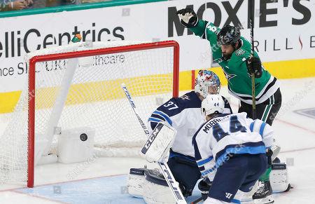 Dallas Stars forward Jamie Benn (14) scores a goal as Winnipeg Jets goaltender Connor Hellebuyck (37) and defenseman Josh Morrissey (44) defend during the third period of an NHL hockey game, in Dallas. Dallas won 5-1