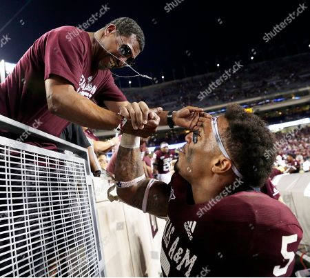 Stock Photo of Texas A&M running back Trayveon Williams (5) shakes hands with his father Thomas Williams in the stands after defeating Kentucky on an airborne touchdown play in overtime at an NCAA college football game, in College Station, Texas