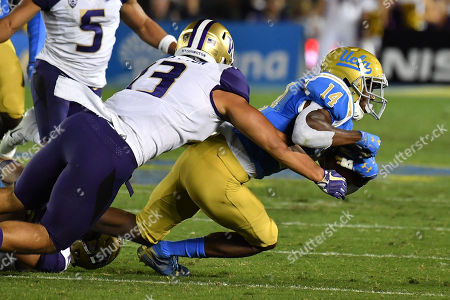 Pasadena, CA.UCLA Bruins wide receiver Theo Howard #14 catches the pass and is tackled by Washington Huskies linebacker Brandon Wellington #13 in action during the fourth quarter of the NCAA Football game between the UCLA Bruins and the Washington Huskies at the Rose Bowl in Pasadena, California