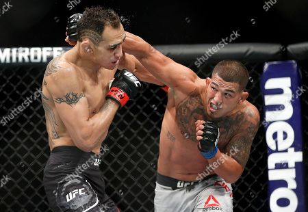 Anthony Pettis, right, punches Tony Ferguson during a lightweight mixed martial arts bout at UFC 229 in Las Vegas