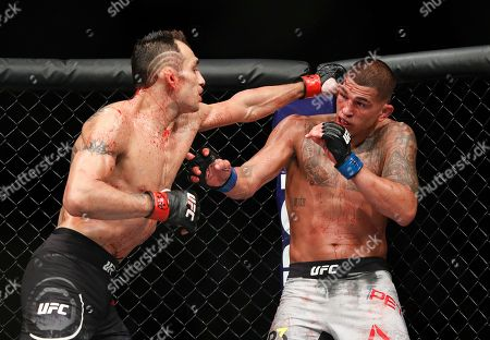 Tony Ferguson, left, punches Anthony Pettis during a lightweight mixed martial arts bout at UFC 229 in Las Vegas