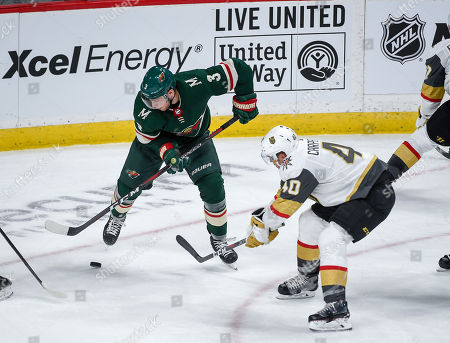 Minnesota Wild right wing Charlie Coyle (3) and Vegas Golden Knights center Ryan Carpenter (40) battle for the puck in the second period during an NHL hockey game, in St. Paul, Minn. The Knights won 2-1 in a shootout
