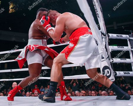 Jarrell Miller, left, knocks down Tomasz Adamek, of Poland, during a heavyweight boxing match, in Chicago