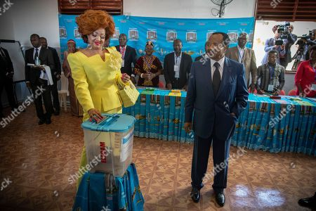 Stock Picture of Cameroon president Paul Biya (R) looks on as his wife Chantal Biya (L) casts her ballot in the presidential elections at a polling station in the capital Yaounde, Cameroon 07 October 2018. Incumbent president Paul Biya is Africa's oldest president and has been in power for 36 years. He faces eight candidates with 6.9 million registered voters. Relations between the government and marginalized Anglophone separatists in the North West and South West of the country is a major issue threatening peace and stability in Cameroon.