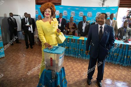 Stock Image of Cameroon president Paul Biya (R) looks on as his wife Chantal Biya (L) casts her ballot in the presidential elections at a polling station in the capital Yaounde, Cameroon, 07 October 2018. Incumbent president Paul Biya is Africa's oldest president and has been in power for 36 years. He faces eight candidates with 6.9 million registered voters. Relations between the government and marginalized Anglophone separatists in the North West and South West of the country is a major issue threatening peace and stability in Cameroon.