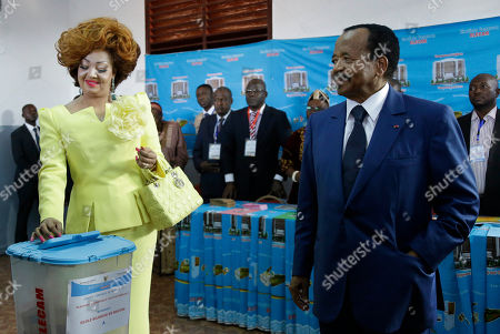 Stock Photo of Cameroon's Incumbent President Paul Biya, right, looks on as his wife Chantal Biya, left, casts her vote during the Presidential elections in Yaounde, Cameroon, . Polls opened Sunday in Cameroon as Africa's oldest leader is widely expected to win another term, while separatists threaten to disrupt the election and many people who have fled the unrest are unable to vote