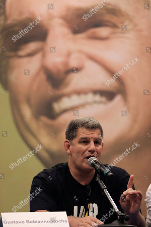 Backdropped by a picture of the presidential candidate Jair Bolsonaro of the Social Liberal Party, Gustavo Bebianno Rocha, president of the Social Liberal Party, speaks to journalists after his candidate spoke in a live broadcast on Facebook, at a hotel in Rio de Janeiro, Brazil, . Official results showed that Workers' Party candidate Fernando Haddad will face Jair Bolsonaro, the far-right congressman in a second-round vote