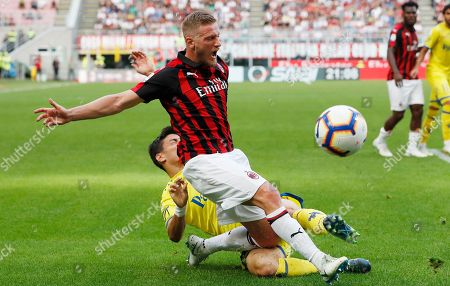 AC Milan's Ignazio Abate, top, is tackled by Chievo's Federico Barba during the Serie A soccer match between AC Milan and Chievo Verona at the San Siro Stadium, in Milan, Italy
