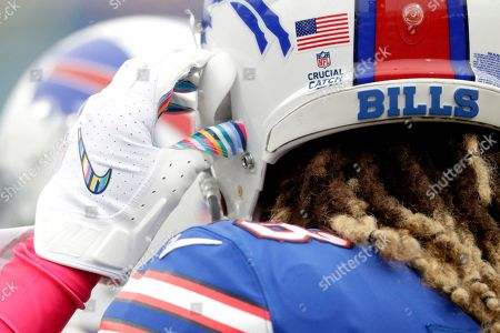Buffalo Bills cornerback Ryan Lewis adjusts hi helmet strap while wearing gloves with crucial catch colors prior to an NFL football game against the Tennessee Titans, in Orchard Park, N.Y