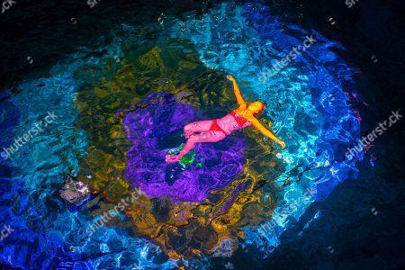 People participate in an art performance on coral death by the Swiss artist Pipilotti Rist entitled 'Toi comme le corail symbiotique' (lit.: You, like the symbiotic coral) in Bern, Switzerland, 07 October 2018. In a public indoor swimming pool, people can immerse themselves in a color world of the oceans specially created to draw attention to the death of corals.