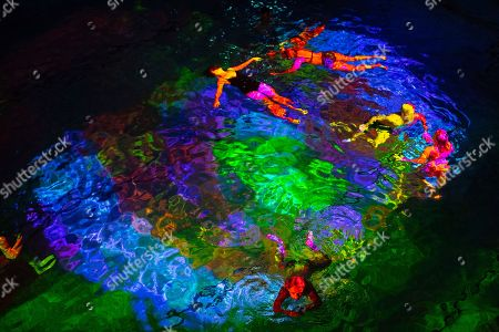 Stock Image of People participate in an art performance on coral death by the Swiss artist Pipilotti Rist entitled 'Toi comme le corail symbiotique' (lit.: You, like the symbiotic coral) in Bern, Switzerland, 07 October 2018. In a public indoor swimming pool, people can immerse themselves in a color world of the oceans specially created to draw attention to the death of corals.