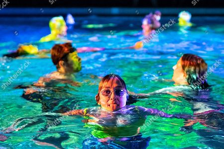 Stock Photo of Swiss artist Pipilotti Rist (C) strikes a pose during her  art performance on coral death entitled 'Toi comme le corail symbiotique' (lit.: You, like the symbiotic coral) in Bern, Switzerland, 07 October 2018. In a public indoor swimming pool, people can immerse themselves in a color world of the oceans specially created to draw attention to the death of corals.