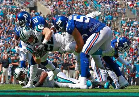 Carolina Panthers' Christian McCaffrey (22) is tackled by New York Giants' Connor Barwin (53) and Landon Collins (21) in the first half of an NFL football game in Charlotte, N.C
