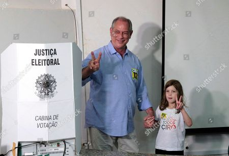 Ciro Gomes, presidential candidate of the Democratic Labor Party, and his granddaughter Maria Clara, flash victory hand signs, after voting in the general elections, in Fortaleza, Brazil, . Brazilians have started trickling to voting booths to choose leaders in an election marked by intense anger at the ruling class following years of political and economic turmoil