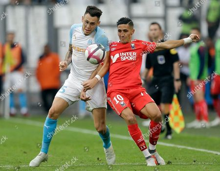 Marseille's Lucas Ocampos, left, challenges Caen's Faycal Fajr for the ball during the League One soccer match between Marseille and Caen at the Velodrome stadium, in Marseille, southern France