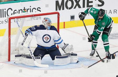 PHOTO. Dallas Stars forward Jamie Benn (14) deflects shot past Winnipeg Jets goaltender Connor Hellebuyck (37) during the third period of an NHL hockey game, in Dallas. Dallas won 5-1