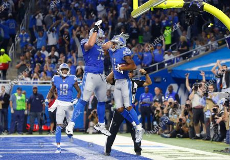 Detroit Lions wide receiver Marvin Jones, right, celebrates his eight-yard touchdown reception with Kenny Wiggins (79) during an NFL football game in Detroit