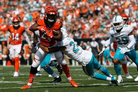 Cincinnati Bengals running back Joe Mixon (28) is tackled by Miami Dolphins cornerback Torry McTyer (24) during the first half of an NFL football game in Cincinnati