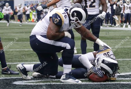 "Los Angeles Rams running back Todd Gurley (30) mimics the ""sleep on the football"" touchdown celebration of Seattle Seahawks running back Mike Davis after Gurley thought he had scored a touchdown (but was ruled not a touchdown on review) during the first half of an NFL football game against the Seattle Seahawks, in Seattle. Los Angeles Rams offensive guard Rodger Saffold (76) looks on"