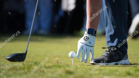 Robbie Fowler places his ball as he prepares to tee off
