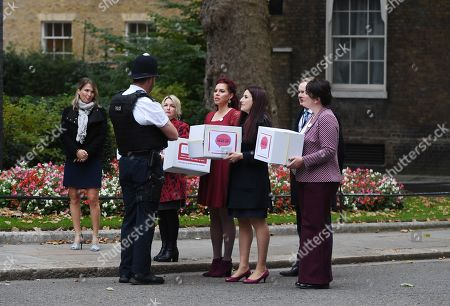 Labour MP Luciana Berger (3-R) and campaigner Natasha Devon (4-R) hand over a petition calling for a law change on Mental Health First Aid, at n10 Downing street in London, Britain, 08 October 2018.