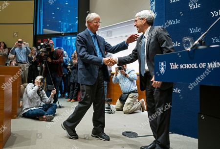 Stock Image of Peter Salovey, President of Yale University, right, welcomes Yale University Professor William Nordhaus, one of the 2018 winners of the Nobel Prize in economics, to the podium just before speaking about the honor, in New Haven, Conn. Nordhaus was named for integrating climate change into long term macroeconomic analysis