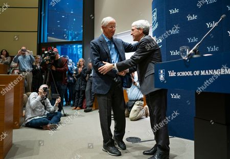 Peter Salovey, President of Yale University, right, welcomes Yale University Professor William Nordhaus, one of the 2018 winners of the Nobel Prize in economics, to the podium just before speaking about the honor, in New Haven, Conn. Nordhaus was named for integrating climate change into long term macroeconomic analysis