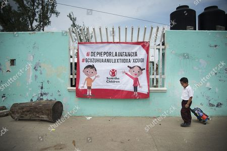 A child walks near a Save The Children poster during a visit by that organization with representatives of the European Union (EU) to the town of San Perdo Huilotepec, in the state of Oaxaca, Mexico, 08 October 2018. A delegation from the European Union (EU) along with Save the Children Mexico visited the southern Mexican state of Oaxaca, where the community block is promoting a project to reactivate the economy of the area and help families affected by the two strong earthquakes of September 2017.