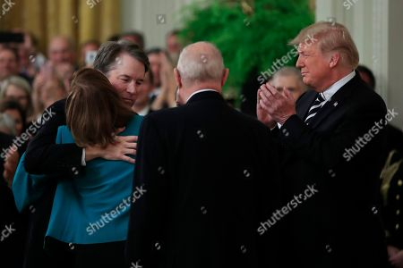 Donald Trump, Brett Kavanaugh, Anthony Kennedy, Ashley Kavanaugh. President Donald Trump, right, applauds as Justice Brett Kavanaugh hugs his wife Ashley Kavanaugh, following a ceremonial swearing-in ceremony of Kavanaugh as Associate Justice of the Supreme Court of the United States conducted by Justice Anthony Kennedy in the East Room of the White House in Washington