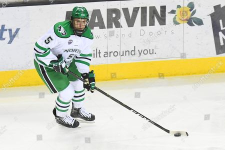 North Dakota Fighting Hawks defenseman Casey Johnson (5) skates with the puck in the third period of an exhibition men's college hockey game between the Manitoba Bisons and the University of North Dakota Fighting Hawks at Ralph Engelstad Arena in Grand Forks. North Dakota won 3-2 in overtime