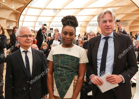 Author Chimamanda Ngozi Adichie (C) Heinrich Riethmueller (L), President of the German Publishers & Booksellers Association and Juergen Boos (R), Director of Frankfurter Buchmesse, pose for a picture prior to the opening press conference of the book fair 'Frankfurter Buchmesse 2018' in Frankfurt Main, Germany, 09 October 2018.  The 70th edition of the international Frankfurt Book Fair, described as the 'world's most important fair for the print and digital content business' runs from 10 to 14 October 2018 and gathers authors, writers and celebrities from all over the world. This year's Guest of Honour country is Georgia.