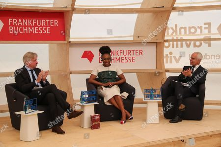 Author Chimamanda Ngozi Adichie (C) is applauded by Heinrich Riethmueller (R), President of the German Publishers & Booksellers Associationon and Juergen Boos (L), Director of Frankfurter Buchmesse, during the opening press conference of the book fair 'Frankfurter Buchmesse 2018' in Frankfurt Main, Germany, 09 October 2018. The 70th edition of the international Frankfurt Book Fair, described as the 'world's most important fair for the print and digital content business' runs from 10 to 14 October 2018 and gathers authors, writers and celebrities from all over the world. This year's Guest of Honour country is Georgia.