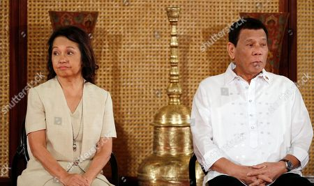Philippine President Rodrigo Duterte, right, and former President and now House Speaker Gloria Macapagal Arroyo prepare to pose with congressmen and other officials during a presentation of Republic Act bills in a ceremony at the Presidential Palace in Manila, Philippines. . Philippine officials say President Rodrigo Duterte has told his Cabinet that medical tests show he doesn't have cancer, but he won't be releasing a public report on his health