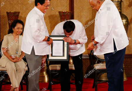 Stock Photo of Rodrigo Duterte, Gloria Macapagal Arroyo, Salvador Medialdea. Philippine President Rodrigo Duterte, center, leans in as he cracks a joke at Labor Secretary Silvestre Bello, second from left, during the presentation of Republic Act bills in a ceremony at the Presidential Palace in Manila, Philippines . Philippine officials say President Rodrigo Duterte has told his Cabinet that medical tests show he doesn't have cancer, but he won't be releasing a public report on his health. At left is former President and now House Speaker Gloria Macapagal Arroyo and at right is Executive Secretary Salvador Medialdea